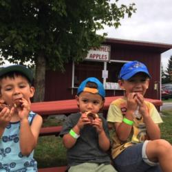 Adorable kids eating apple cider donuts